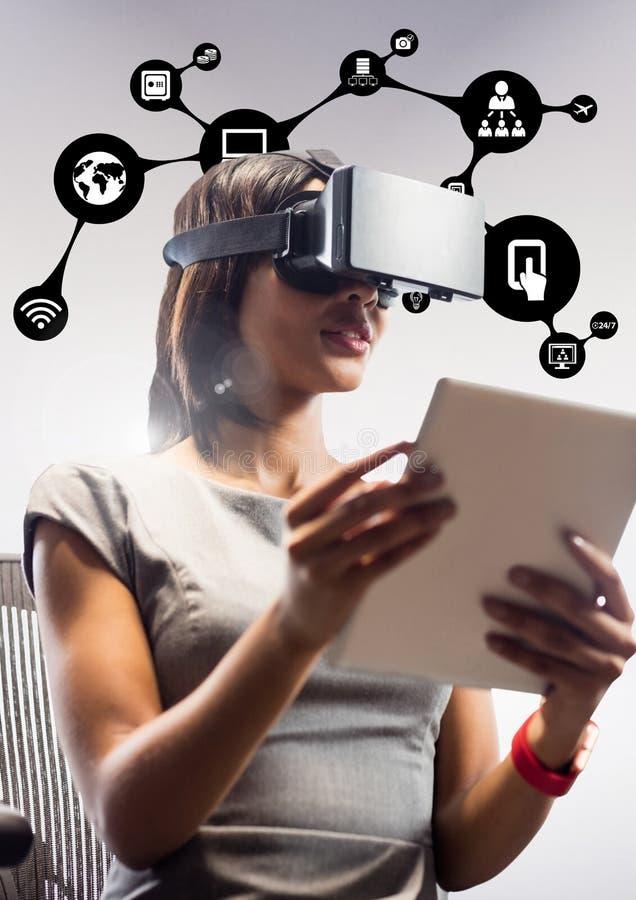 Mulher que usa auriculares da realidade virtual e a tabuleta digital contra ícones da aplicação foto de stock