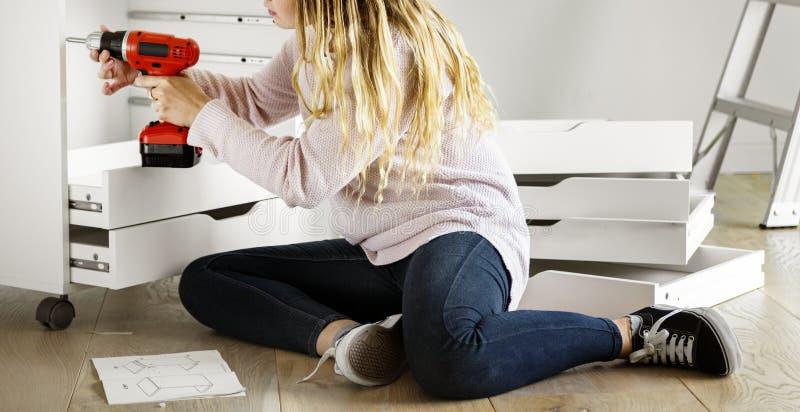 A mulher que usa a broca eletrônica instala o armário fotografia de stock