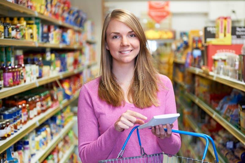 Mulher que usa a calculadora enquanto comprando no supermercado imagens de stock