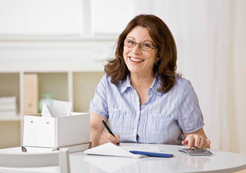 Mulher que usa a calculadora para pagar contas mensais fotos de stock royalty free