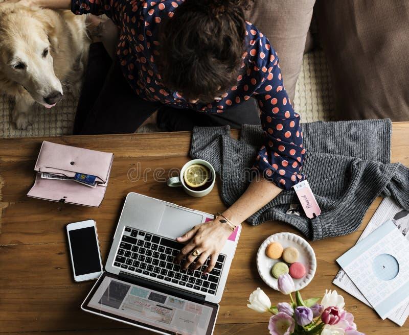 Mulher que usa a compra do portátil em linha e o cão das trocas de carícias imagem de stock royalty free