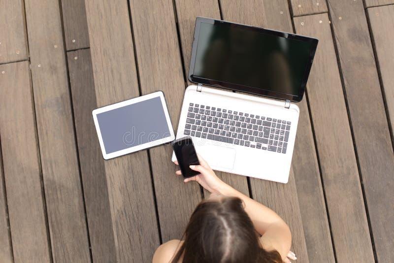 A mulher que usa dispositivos múltiplos telefona ao portátil e à tabuleta