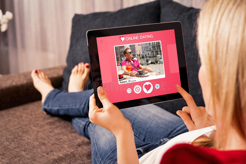 Mulher que usa em linha datar o app na tabuleta fotos de stock