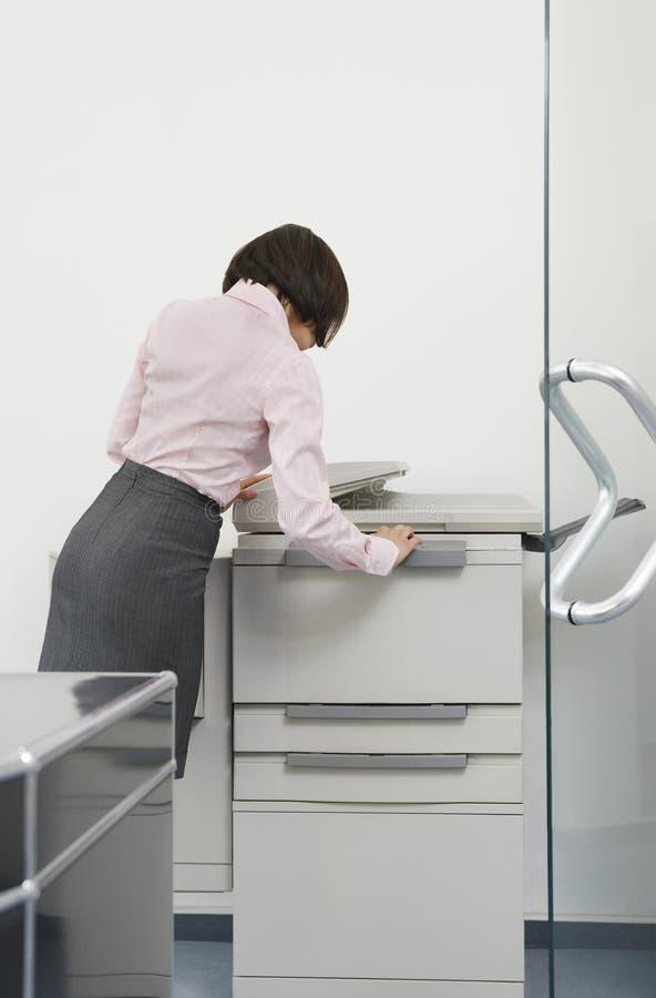 Mulher que usa a fotocopiadora no escritório imagens de stock royalty free