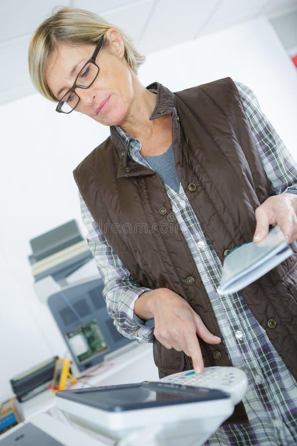 Mulher que usa a fotocopiadora no escritório criativo fotos de stock royalty free