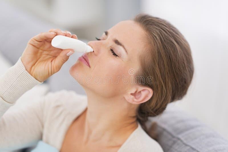 Mulher que usa gotas nasais imagem de stock
