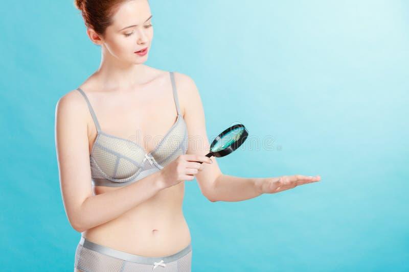 Mulher que usa a lupa para examinar sua pele das toupeiras imagem de stock