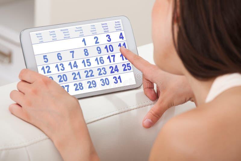 Mulher que usa o calendário na tabuleta digital em casa