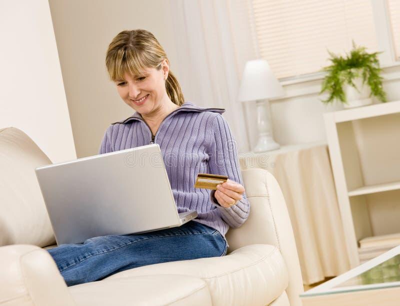 Mulher que usa o cartão de crédito para comprar bens foto de stock