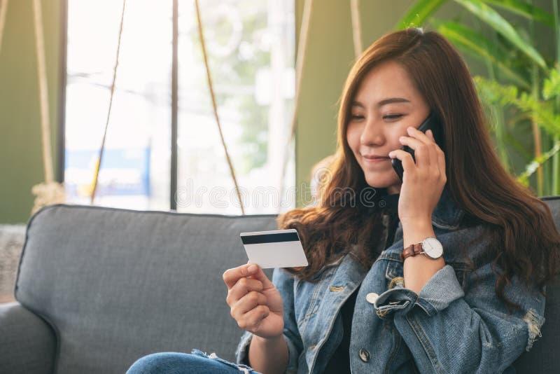 Mulher que usa o cartão de crédito para comprar e comprar em linha ao falar no telefone celular imagens de stock royalty free