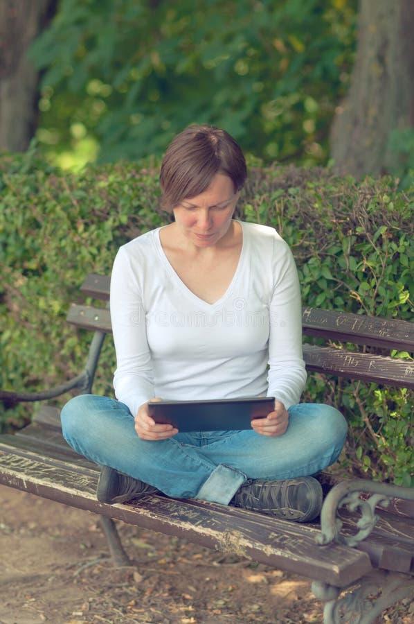 Mulher que usa o computador digital da tabuleta imagem de stock
