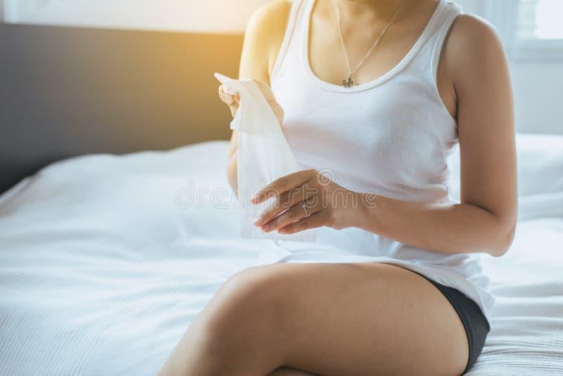 Mulher que usa o lenço de papel com sopro do frio e o nariz ralo na cama, mulher doente que espirra, conceito da saúde imagem de stock royalty free