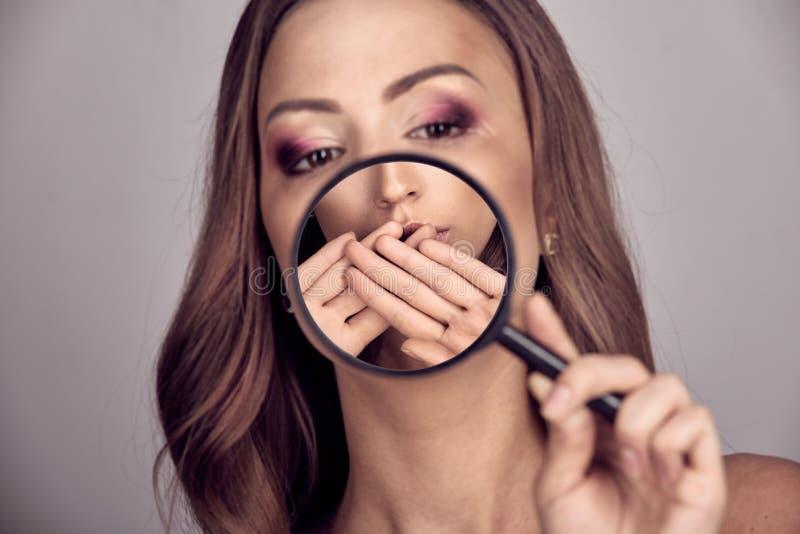 Mulher que usa o magnifier imagens de stock