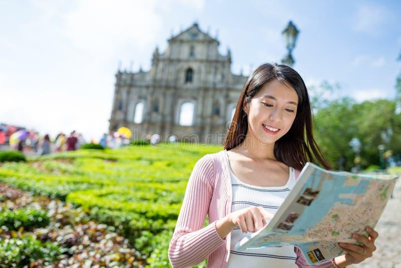 Mulher que usa o mapa da cidade na cidade de Macau fotografia de stock
