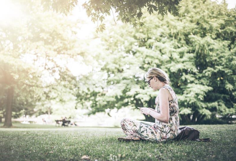 Mulher que usa o parque do smartphone em público fotos de stock royalty free