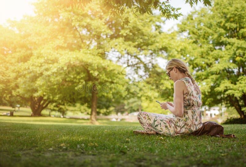 Mulher que usa o parque do smartphone em público imagens de stock royalty free