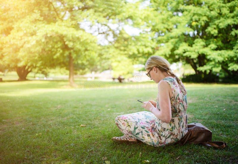 Mulher que usa o parque do smartphone em público imagens de stock
