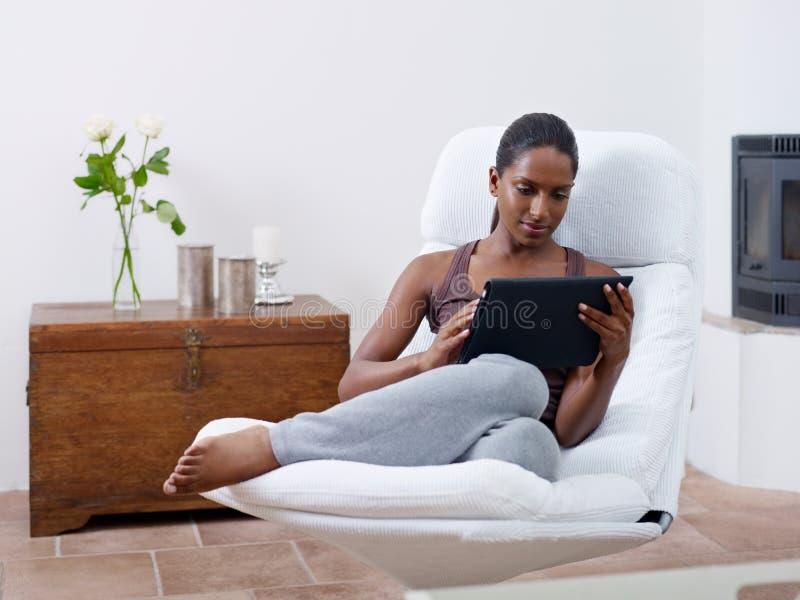 Mulher que usa o PC da tabuleta em casa foto de stock royalty free