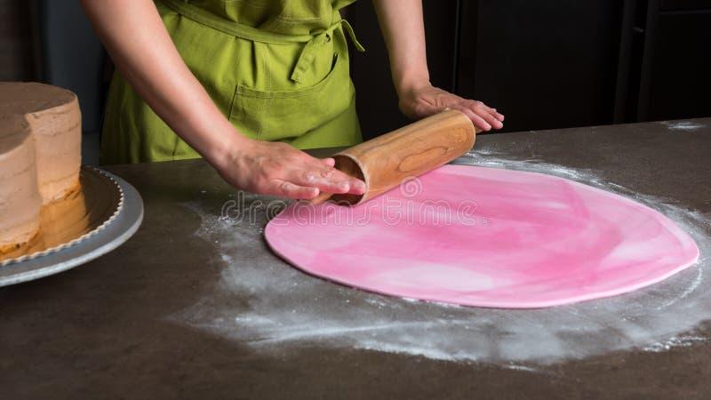Mulher que usa o pino do rolo que prepara o fundente cor-de-rosa para a decoração do bolo foto de stock