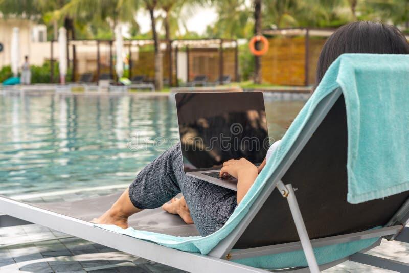 Mulher que usa o portátil ao sentar-se no banco na piscina fotografia de stock