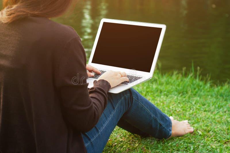 Mulher que usa o portátil da tela vazia em um ar livre imagem de stock royalty free