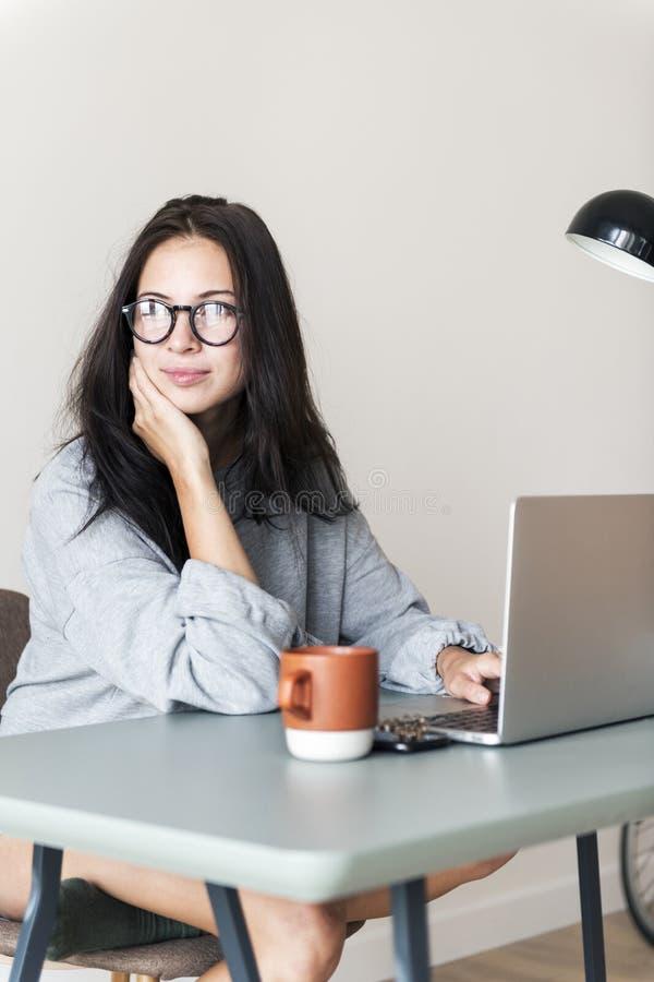 Mulher que usa o portátil do computador em sua sala fotos de stock