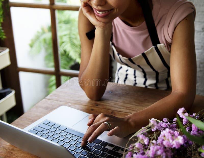 Mulher que usa o portátil do computador no florista foto de stock royalty free