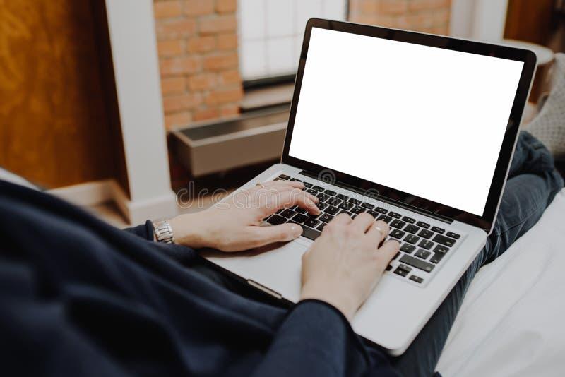 Mulher que usa o portátil em sua cama imagens de stock royalty free