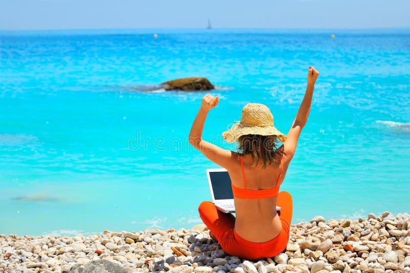 Mulher que usa o portátil na praia imagens de stock
