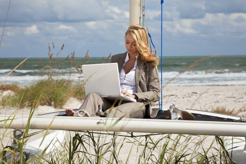 Mulher que usa o portátil no barco na praia