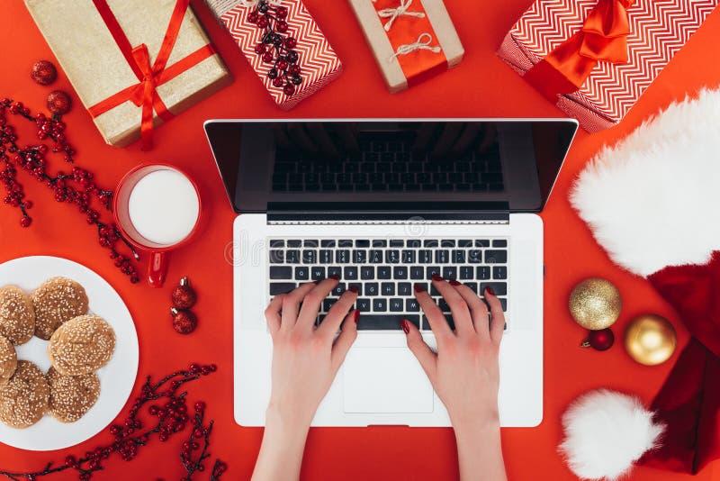 Mulher que usa o portátil no christmastime fotografia de stock