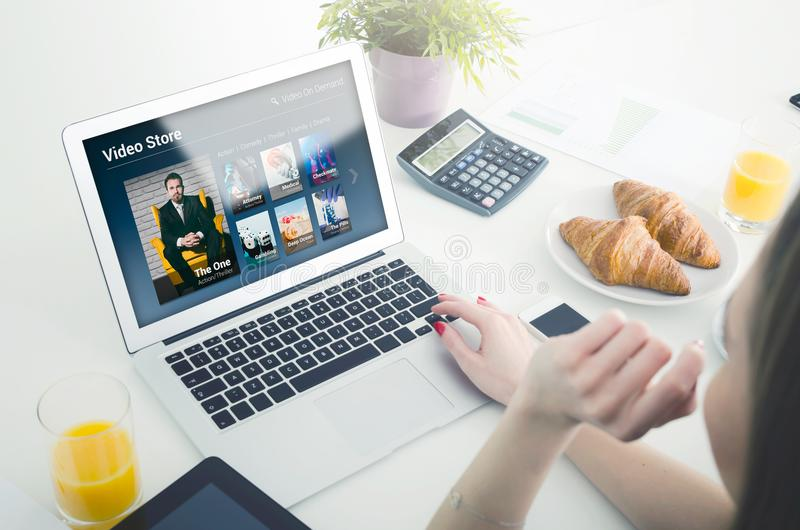 Mulher que usa o portátil para o filme de observação no serviço de VOD fotos de stock royalty free