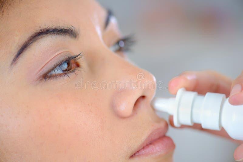 Mulher que usa o pulverizador nasal imagem de stock royalty free