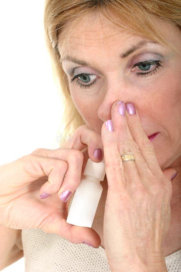 Mulher que usa o pulverizador nasal com mão imagens de stock royalty free