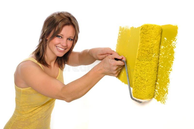 Mulher que usa o rolo de pintura com amarelo fotografia de stock royalty free