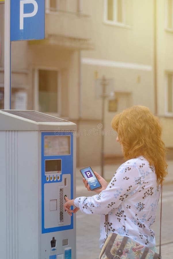 Mulher que usa o smartphone app para pagar estacionar fotografia de stock