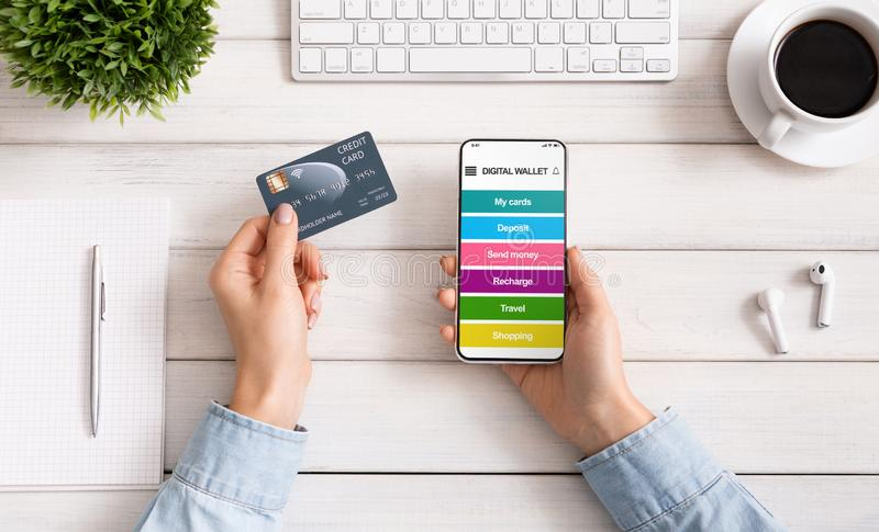 Mulher que usa o smartphone com o cartão digital da aplicação e de crédito da carteira imagem de stock
