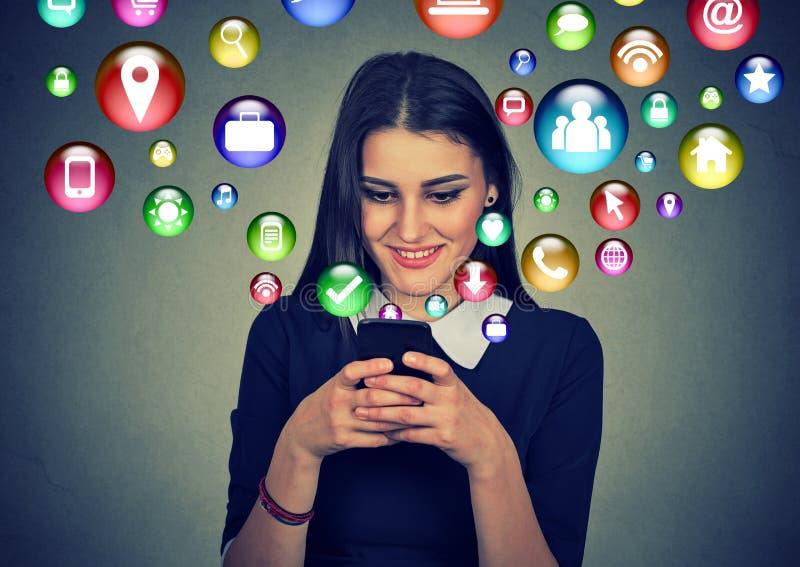 Mulher que usa o smartphone com os ícones da aplicação que voam fora da tela ilustração stock