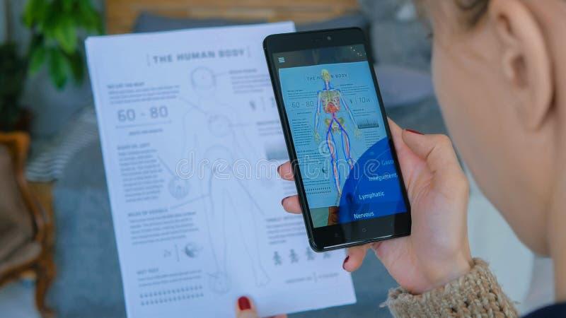 Mulher que usa o smartphone com realidade aumentada app imagem de stock