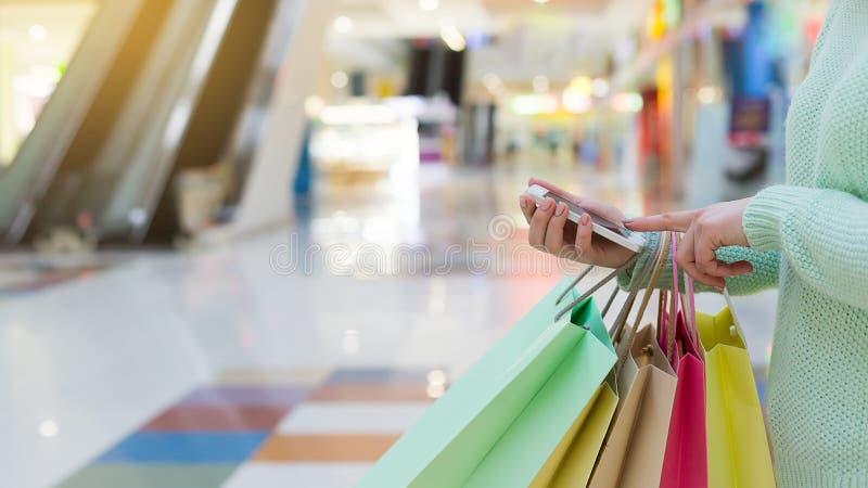 Mulher que usa o smartphone e guardando sacos de compras imagens de stock royalty free
