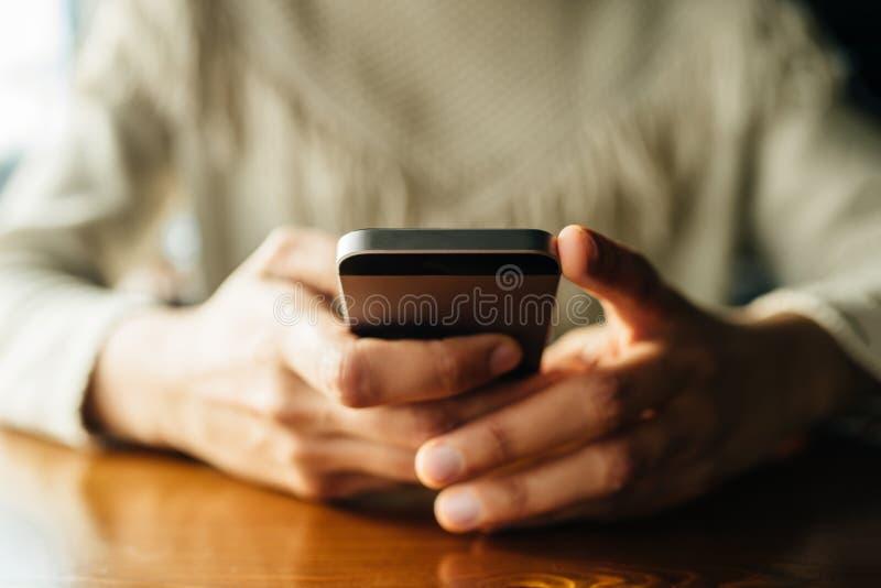 Mulher que usa o smartphone na tabela de madeira no caf? imagens de stock