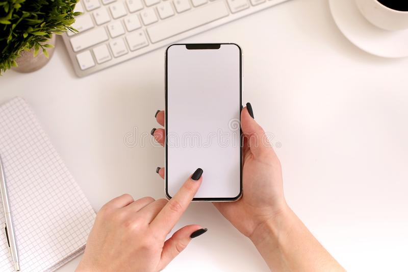 Mulher que usa o smartphone no trabalho Tela vazia branca, vista superior fotografia de stock royalty free