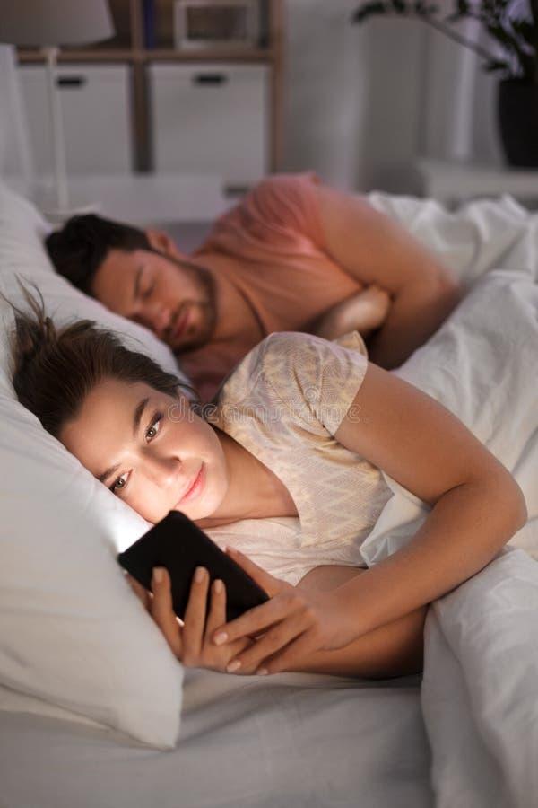 Mulher que usa o smartphone quando o noivo dormir foto de stock royalty free
