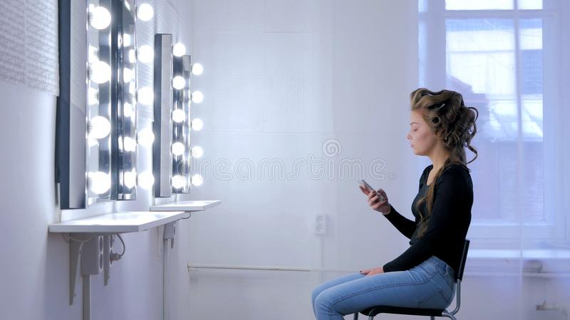 Mulher que usa o smartphone que senta-se na frente do espelho imagens de stock