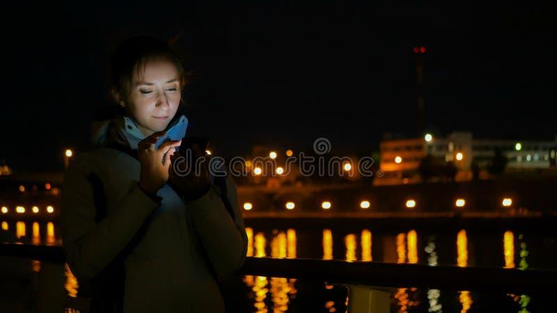 Mulher que usa o smartphone vertical na plataforma do navio de cruzeiros na noite fotos de stock royalty free