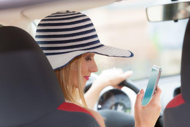 Mulher que usa o telefone ao conduzir seu carro fotos de stock royalty free
