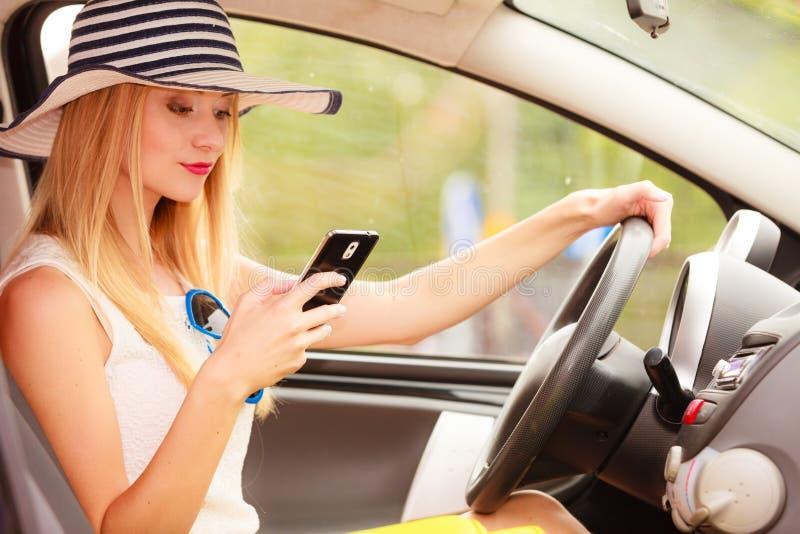 Mulher que usa o telefone ao conduzir seu carro imagens de stock