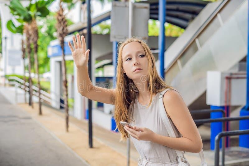 Mulher que usa o telefone app para o serviço de saudação do passeio do táxi ou usando o pho fotografia de stock
