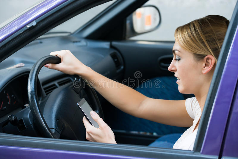 Mulher que usa o telefone celular ao conduzir o carro imagem de stock royalty free