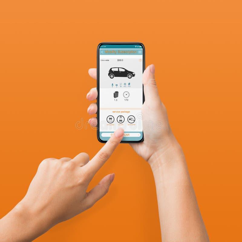 Mulher que usa o telefone celular com o app do aluguel do carro na tela fotos de stock